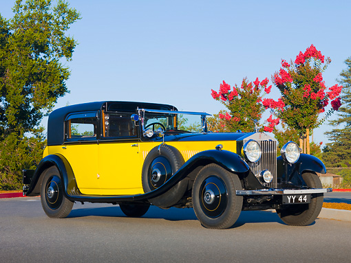 AUT 19 RK0707 01 © Kimball Stock 1931 Rolls-Royce Phantom II Yellow And Black 3/4 Front View On Pavement By Trees