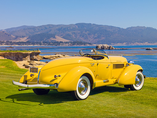AUT 19 RK0719 01 © Kimball Stock 1935 Auburn 851 Speedster Yellow 3/4 Rear View On Grass By Water