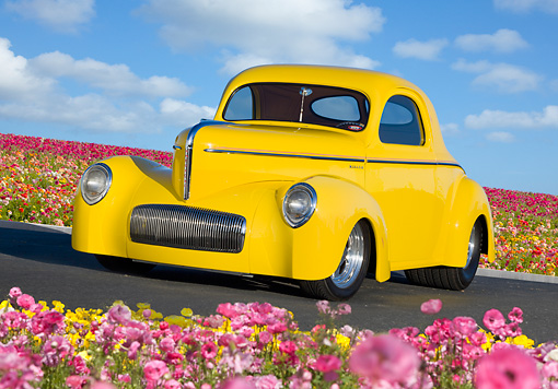 AUT 20 BK0002 01 © Kimball Stock 1941 Willys Coupe Yellow 3/4 Front View On Pavement By Field Of Flowers