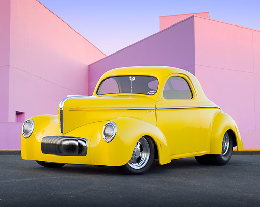 AUT 20 BK0003 01 © Kimball Stock 1941 Willys Coupe Yellow 3/4 Front View On Pavement By Pink Building