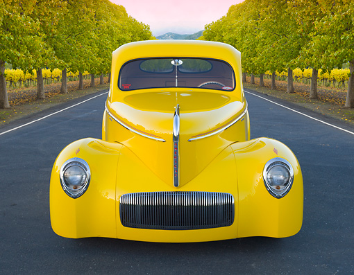 AUT 20 BK0004 01 © Kimball Stock 1941 Willys Coupe Yellow Front View On Pavement By Row Of Trees