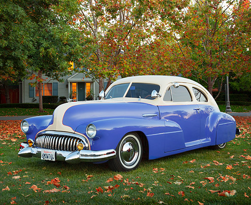 AUT 20 BK0005 01 © Kimball Stock 1947 Buick Sedanette Blue And White 3/4 Front View On Grass By House And Autumn Trees