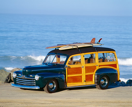 AUT 20 RK0006 03 © Kimball Stock 1946 Ford Woody With Surfboards 3/4 Side View On Sand By Ocean
