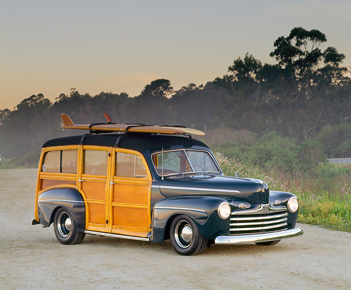 AUT 20 RK0014 04 © Kimball Stock 1946 Ford Woodie Green With Surfboard 3/4 Side View On Road By Trees