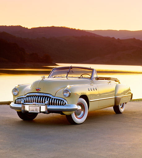 AUT 20 RK0083 08 © Kimball Stock 1949 Buick Roadmaster Convertible Yellow Front 3/4 View On Road By Water At Dusk