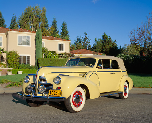 AUT 20 RK0203 02 © Kimball Stock 1940 Buick Phaeton Limited Convertible Yellow 3/4 Front View On Pavement By House