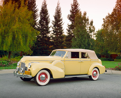 AUT 20 RK0210 01 © Kimball Stock 1940 Buick Phaeton Limited Convertible Yellow 3/4 Side View On Pavement By Trees Filtered