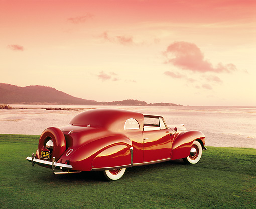 AUT 20 RK0254 02 © Kimball Stock 1940 Lincoln Continental Convertible Coupe Red 3/4 Rear View On Grass By Water