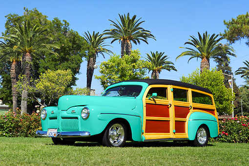 AUT 20 RK0291 01 © Kimball Stock 1942 Ford Woodie Green 3/4 Side View On Grass By Trees