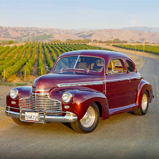 AUT 20 RK0397 01 © Kimball Stock 1941 Chevrolet Special Deluxe Coupe Burgundy 3/4 Front View On Pavement By Vineyard