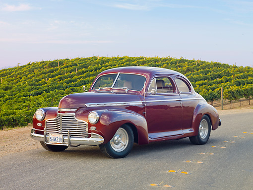 AUT 20 RK0398 01 © Kimball Stock 1941 Chevrolet Special Deluxe Coupe Burgundy 3/4 Front View On Pavement By Vineyard