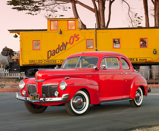 AUT 20 RK0402 01 © Kimball Stock 1941 Mercury Club Coupe Red 3/4 Front View On Pavement By Train