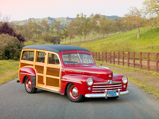 AUT 20 RK0478 01 © Kimball Stock 1947 Ford Woodie Red 3/4 Front View On Pavement By Fence And Grassy Hill
