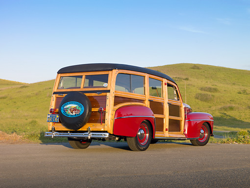 AUT 20 RK0480 01 © Kimball Stock 1947 Ford Woodie Red 3/4 Rear View On Pavement By Grassy Hill