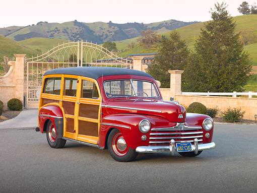 AUT 20 RK0481 01 © Kimball Stock 1947 Ford Woodie Red 3/4 Front View On Pavement By Gate And Grassy Hills