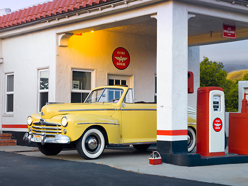 AUT 20 RK0512 01 © Kimball Stock 1947 Ford Super Deluxe Convertible Yellow 3/4 Front View In Gas Station