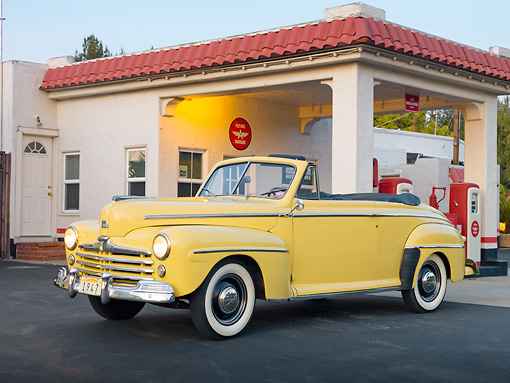 AUT 20 RK0513 01 © Kimball Stock 1947 Ford Super Deluxe Convertible Yellow 3/4 Front View In Gas Station