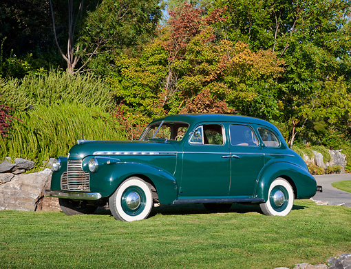 AUT 20 RK0528 01 © Kimball Stock 1940 Chevrolet Sedan Deluxe Green 3/4 Side View On Grass By Trees