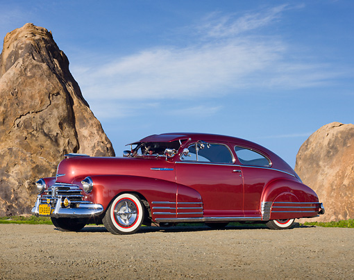 AUT 20 RK0536 01 © Kimball Stock 1948 Chevrolet Fleetline Aerosedan Custom Burgundy 3/4 Side View On Gravel By Tall Rocks