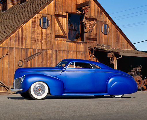 AUT 20 RK0540 01 © Kimball Stock 1940 Mercury Coupe Blue Profile View On Pavement By Old Wooden Barn