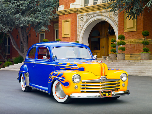 AUT 20 RK0542 01 © Kimball Stock 1948 Ford 2-Door Sedan Blue With Yellow Flames 3/4 Front View On Pavement By Brick Building