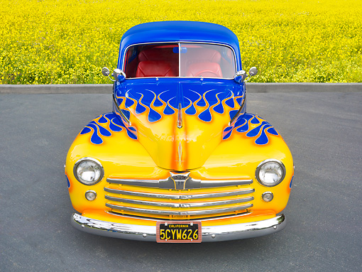 AUT 20 RK0547 01 © Kimball Stock 1948 Ford 2-Door Sedan Blue With Yellow Flames Front View On Pavement By Field Of Wildflowers