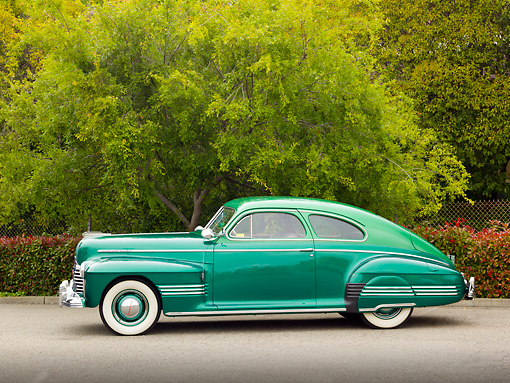 AUT 20 RK0552 01 © Kimball Stock 1941 Pontiac Torpedo Streamliner Two-Tone Green Profile View On Pavement By Trees