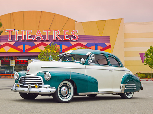 AUT 20 RK0556 01 © Kimball Stock 1946 Chevrolet Fleetmaster White Pearl And Forest Green 3/4 Front View On Pavement By Movie Theater
