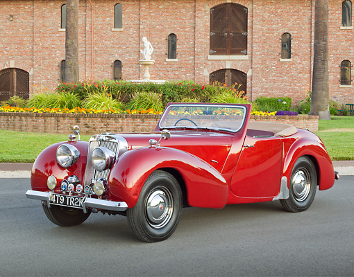 AUT 20 RK0576 01 © Kimball Stock 1949 Triumph 2000 Roadster Red 3/4 Front View On Pavement By Brick Building