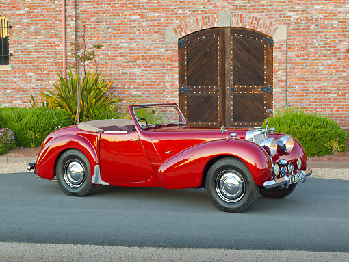 AUT 20 RK0579 01 © Kimball Stock 1949 Triumph 2000 Roadster Red 3/4 Side View On Pavement By Brick Building