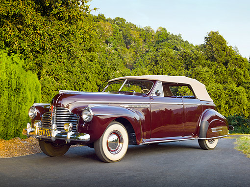 AUT 20 RK0589 01 © Kimball Stock 1941 Buick Roadmaster Phaeton 71C Titan Maroon 3/4 Front View On Pavement By Trees