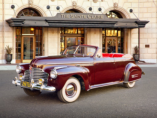 AUT 20 RK0592 01 © Kimball Stock 1941 Buick Roadmaster Phaeton 71C Titan Maroon 3/4 Front View On Pavement By Front Of Hotel