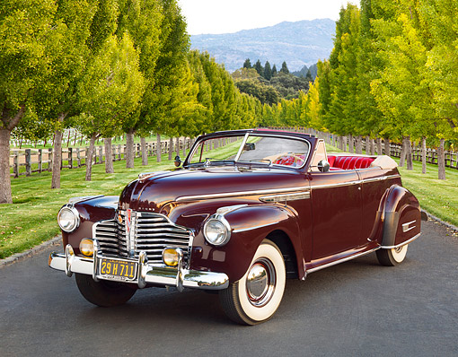 AUT 20 RK0593 01 © Kimball Stock 1941 Buick Roadmaster Phaeton 71C Titan Maroon 3/4 Front View On Pavement By Rows Of Trees