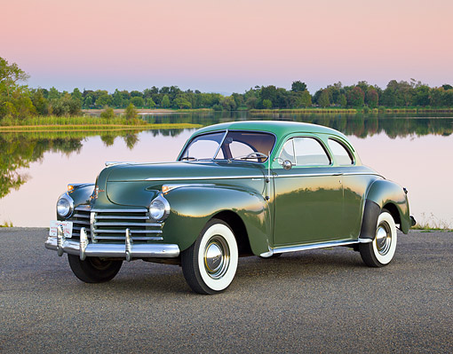 AUT 20 RK0595 01 © Kimball Stock 1941 Chrysler C30 Saratoga Club Coupe Green 3/4 Front View On Pavement By Water At Dusk