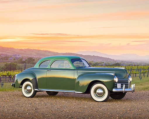 AUT 20 RK0599 01 © Kimball Stock 1941 Chrysler C30 Saratoga Club Coupe Polo Green Light Over Dark 3/4 Side View On Gravel By Vineyard At Dusk