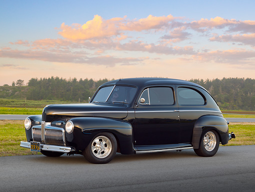 AUT 20 RK0610 01 © Kimball Stock 1942 Ford 2-Door Sedan Black 3/4 Side View On Pavement By Grass And Trees At Dusk