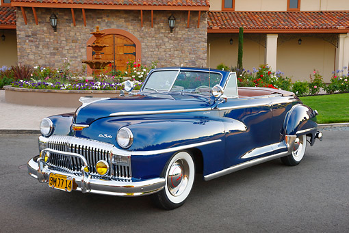AUT 20 RK0614 01 © Kimball Stock 1948 DeSoto Custom Regal Blue 3/4 Front View On Pavement By Building