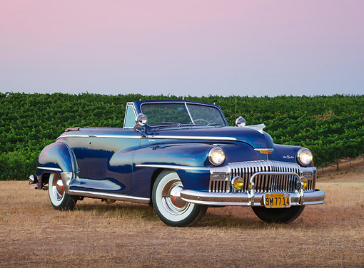 AUT 20 RK0629 01 © Kimball Stock 1948 DeSoto Custom Regal Blue 3/4 Side View On Grass By Vineyard At Dusk