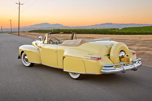 AUT 20 RK0647 01 © Kimball Stock 1947 Lincoln Continental Yellow 3/4 Rear View On Pavement By Vineyard At Dusk