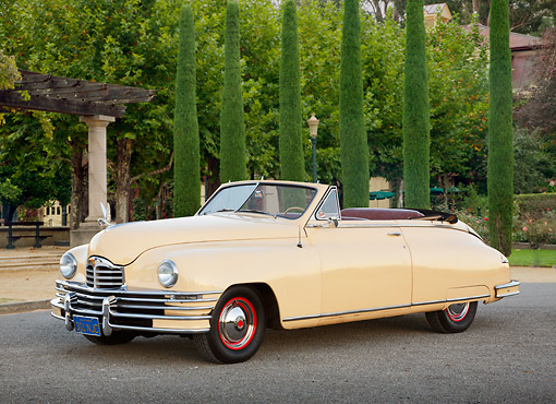AUT 20 RK0650 01 © Kimball Stock 1948 Packard Super 8 Convertible Arizona Beige 3/4 Front View On Pavement By Shrubs