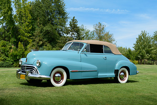 AUT 20 RK0659 01 © Kimball Stock 1947 Oldsmobile Series 68 Convertible Caspian Blue 3/4 Side View On Grass By Trees