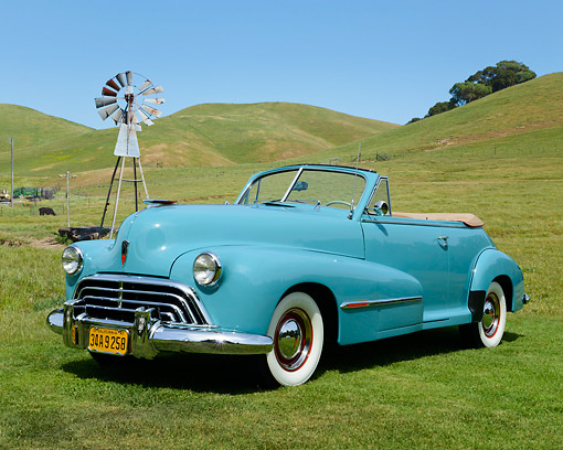 AUT 20 RK0660 01 © Kimball Stock 1947 Oldsmobile Series 68 Convertible Caspian Blue 3/4 Front View On Grass By Old Windmill