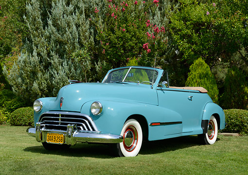 AUT 20 RK0661 01 © Kimball Stock 1947 Oldsmobile Series 68 Convertible Caspian Blue 3/4 Front View On Grass By Trees