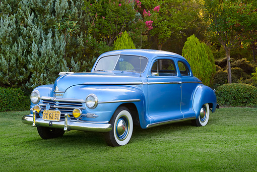 AUT 20 RK0663 01 © Kimball Stock 1947 Plymouth Special Deluxe Coupe Blue 3/4 Front View On Grass By Trees
