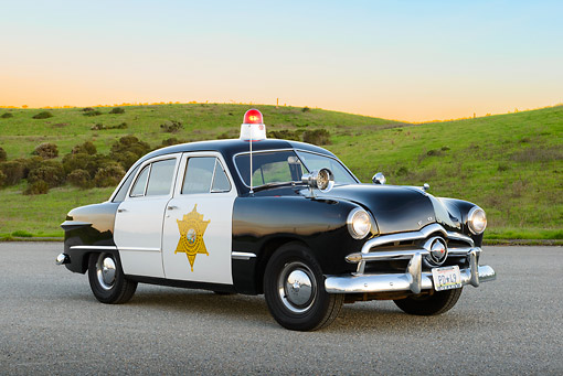 AUT 20 RK0666 01 © Kimball Stock 1949 Ford Police Car 3/4 Front View On Pavement By Grassy Hills At Dusk