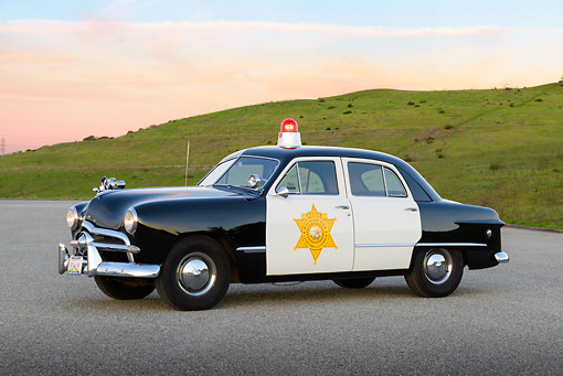AUT 20 RK0667 01 © Kimball Stock 1949 Ford Police Car 3/4 Side View On Pavement By Grassy Hills At Dusk