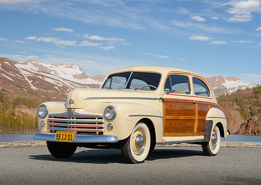 AUT 20 RK0679 01 © Kimball Stock 1947 Ford Super Deluxe 6 Sportsman Cream 3/4 Front View On Pavement By Water And Mountains