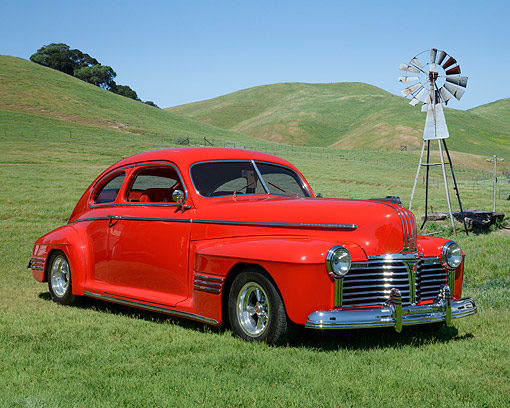 AUT 20 RK0683 01 © Kimball Stock 1941 Pontiac Torpedo Streamliner Sedan Red 3/4 Front View On Grass By Windmill