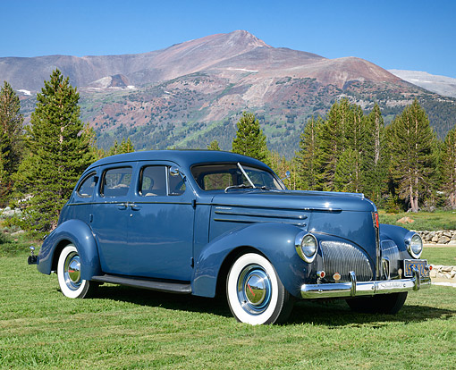 AUT 20 RK0691 01 © Kimball Stock 1940 Studebaker Commander Blue 3/4 Front View On Grass By Mountains