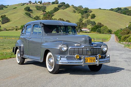 AUT 20 RK0706 01 © Kimball Stock 1947 Mercury Town Sedan Gunmetal Gray 3/4 Front View On Pavement By Grassy Hills